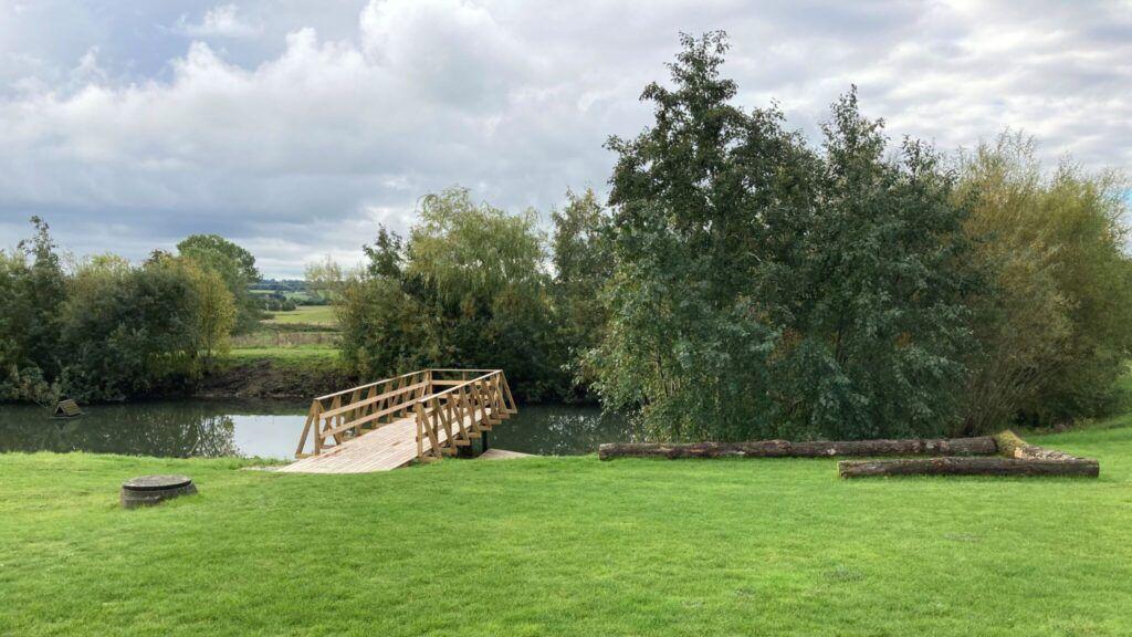 Billedet viser en bro, der går ud over et regnvandsbassin
